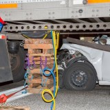 Car wedged under semi